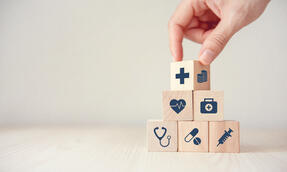 health-insurance-concept-reduce-medical-expenses-hand-flip-wood-cube-with-icon-healthcare-medical-and-coin-on-wood-background-copy-space